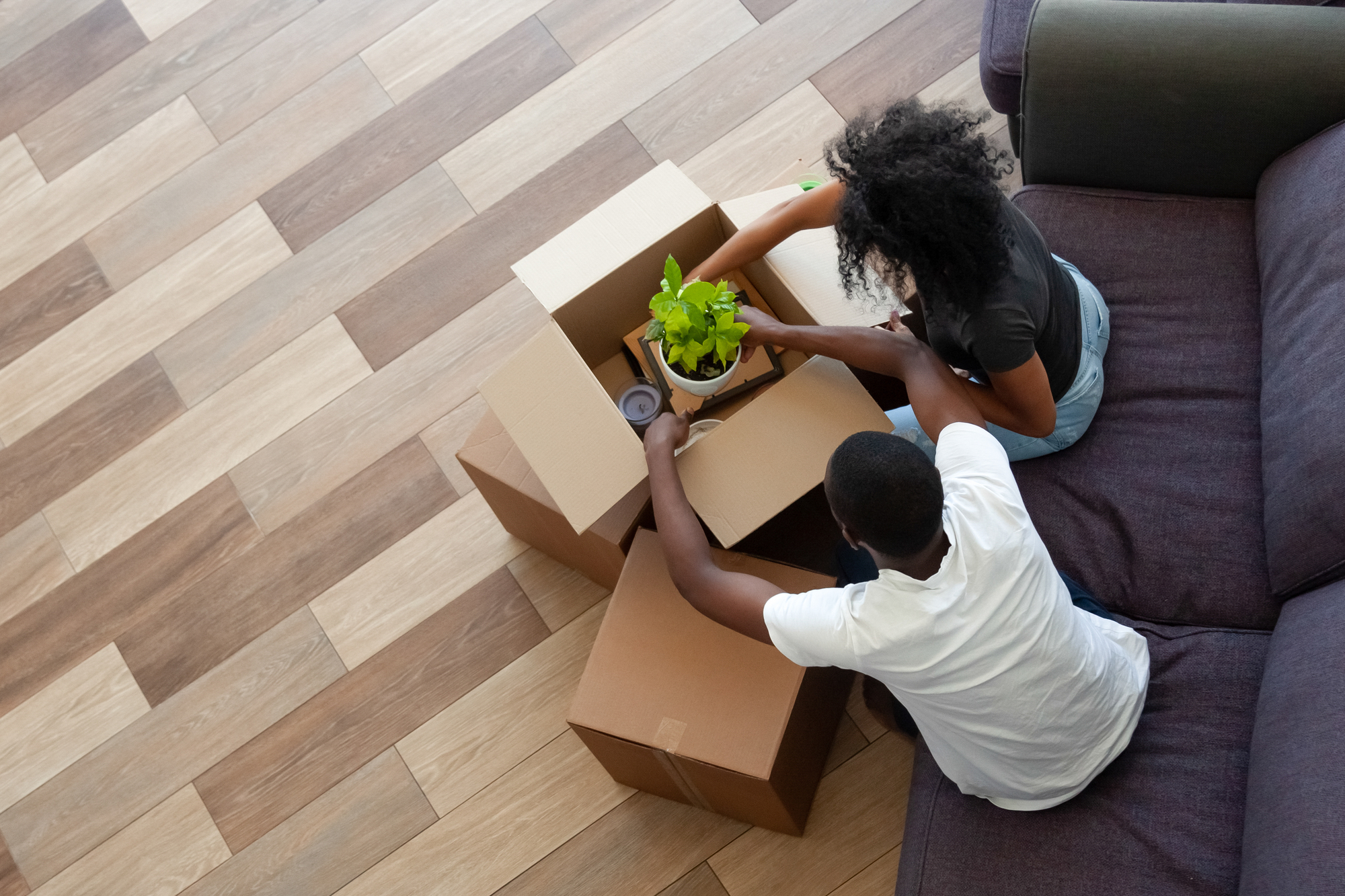 Black couple unpacking cardboard boxes in living room moving in out new home, african tenants renters packing stuff preparing for relocation house renovation