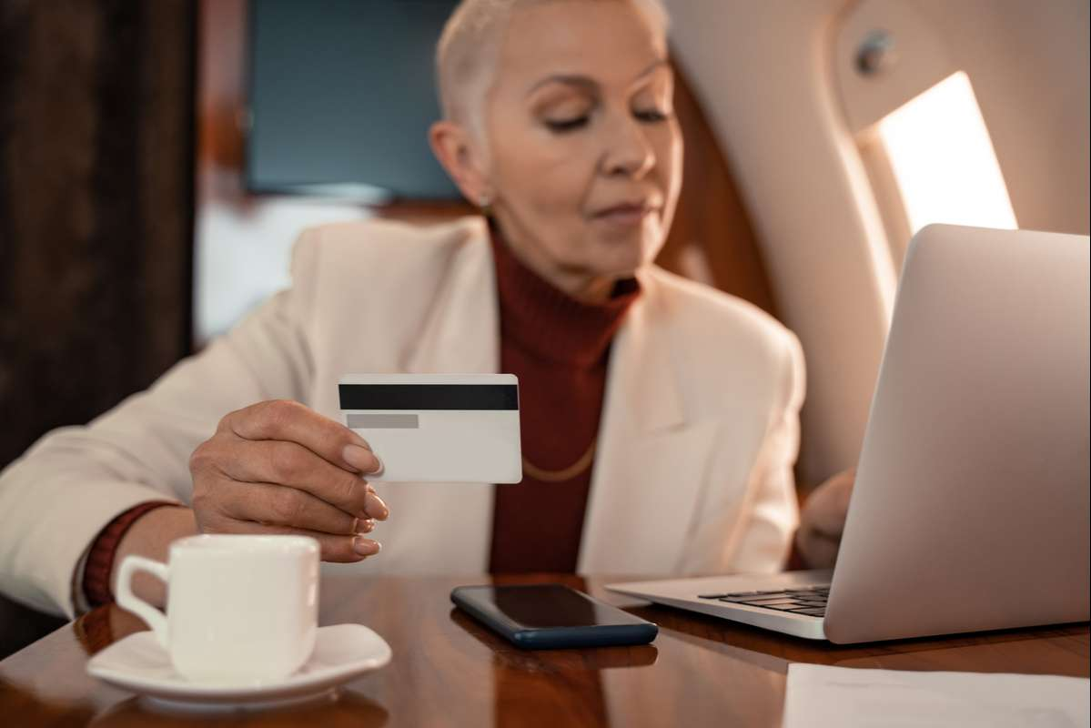 Credit card in hand of blurred businesswoman using laptop near coffee in plane (R) (S)