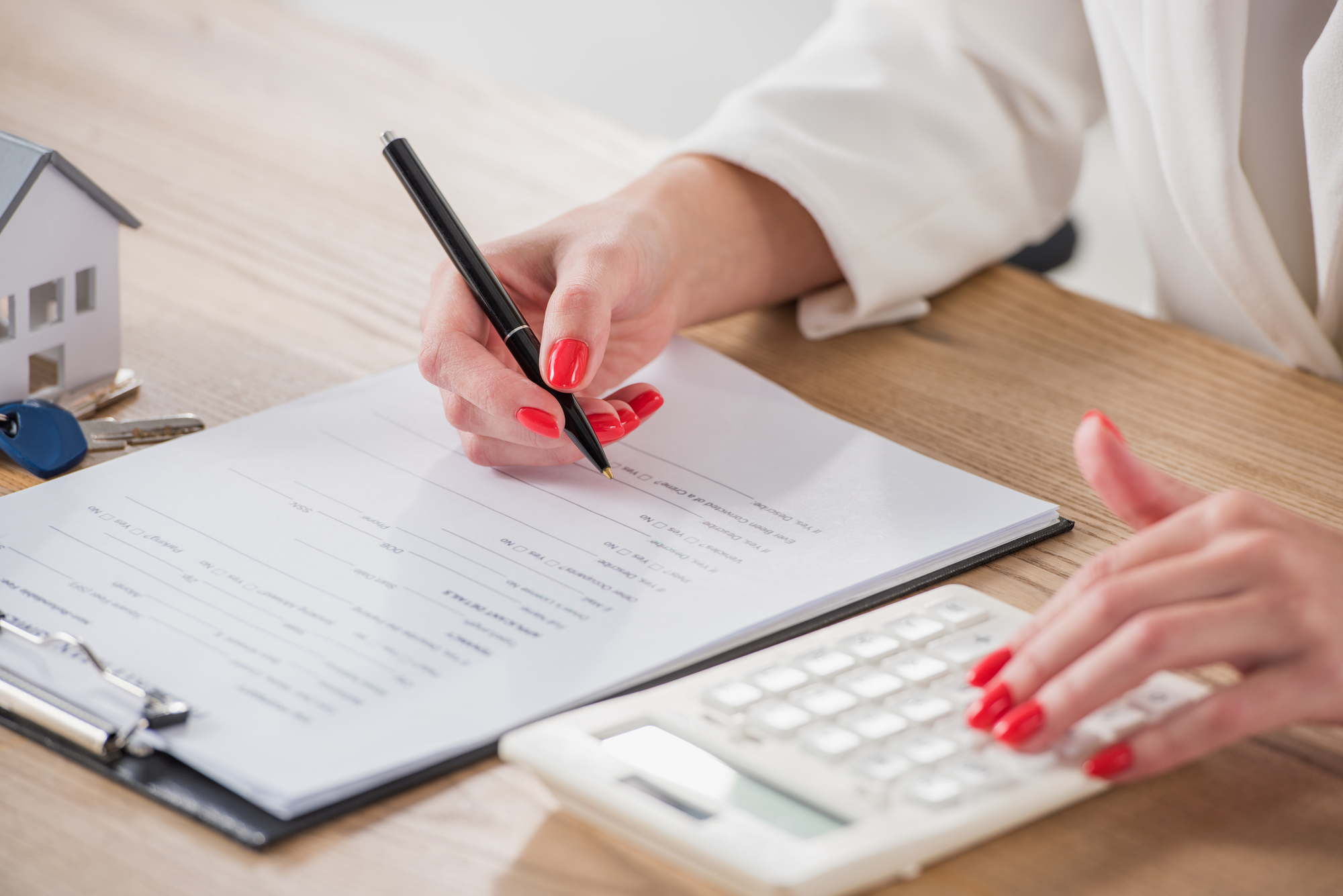 Cropped view of businesswoman using calculator and writing in contract near house model and keys