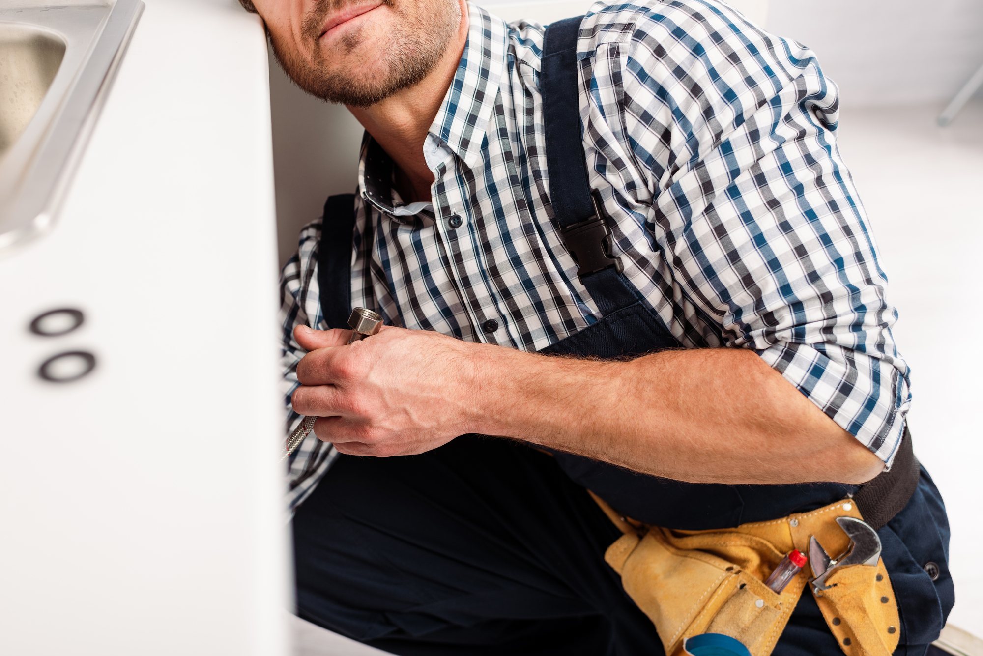 Cropped view of plumber holding metal pipe while repairing sink in kitchen