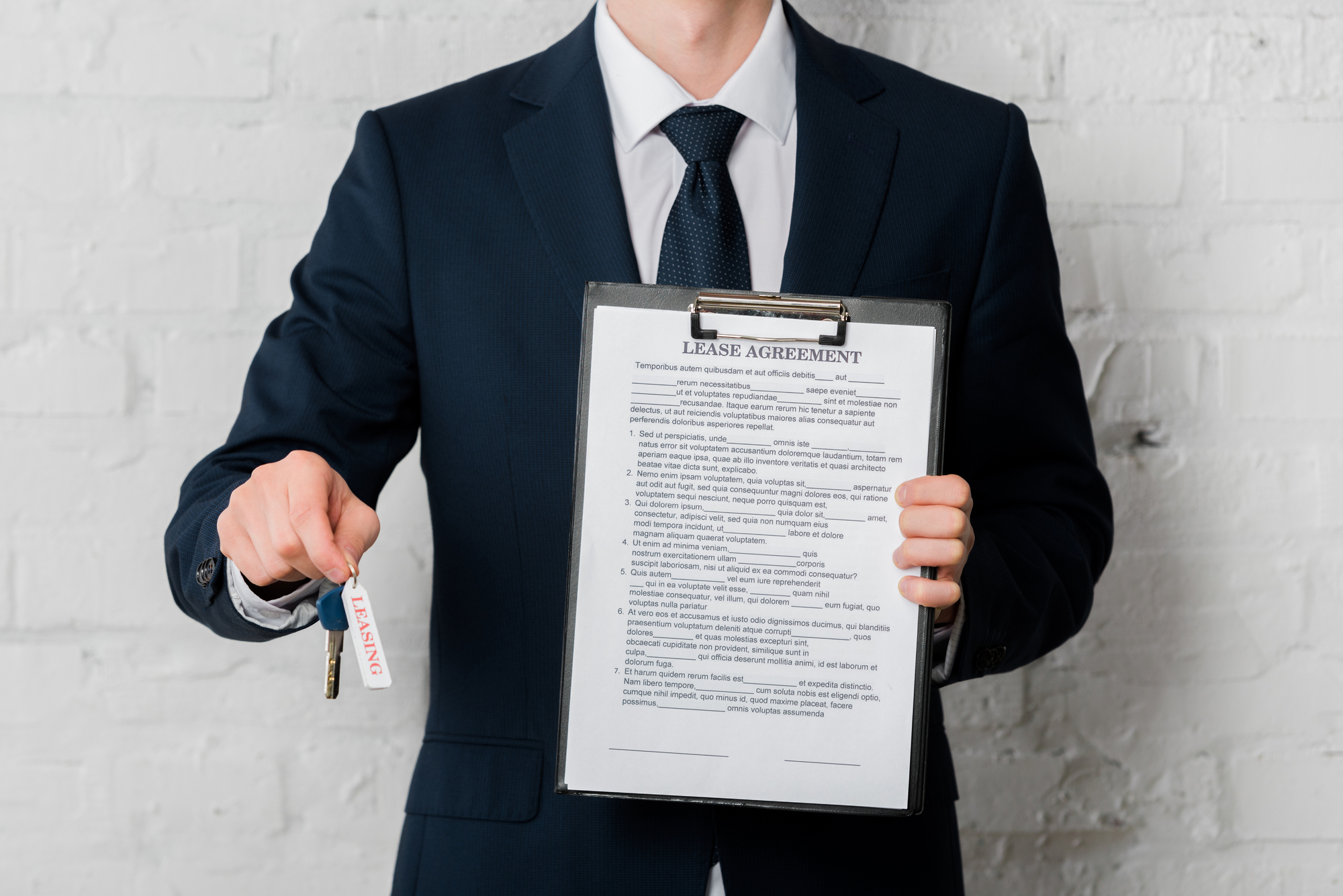 Cropped view of realtor in suit holding key with leasing lettering and clipboard with lease agreement on white