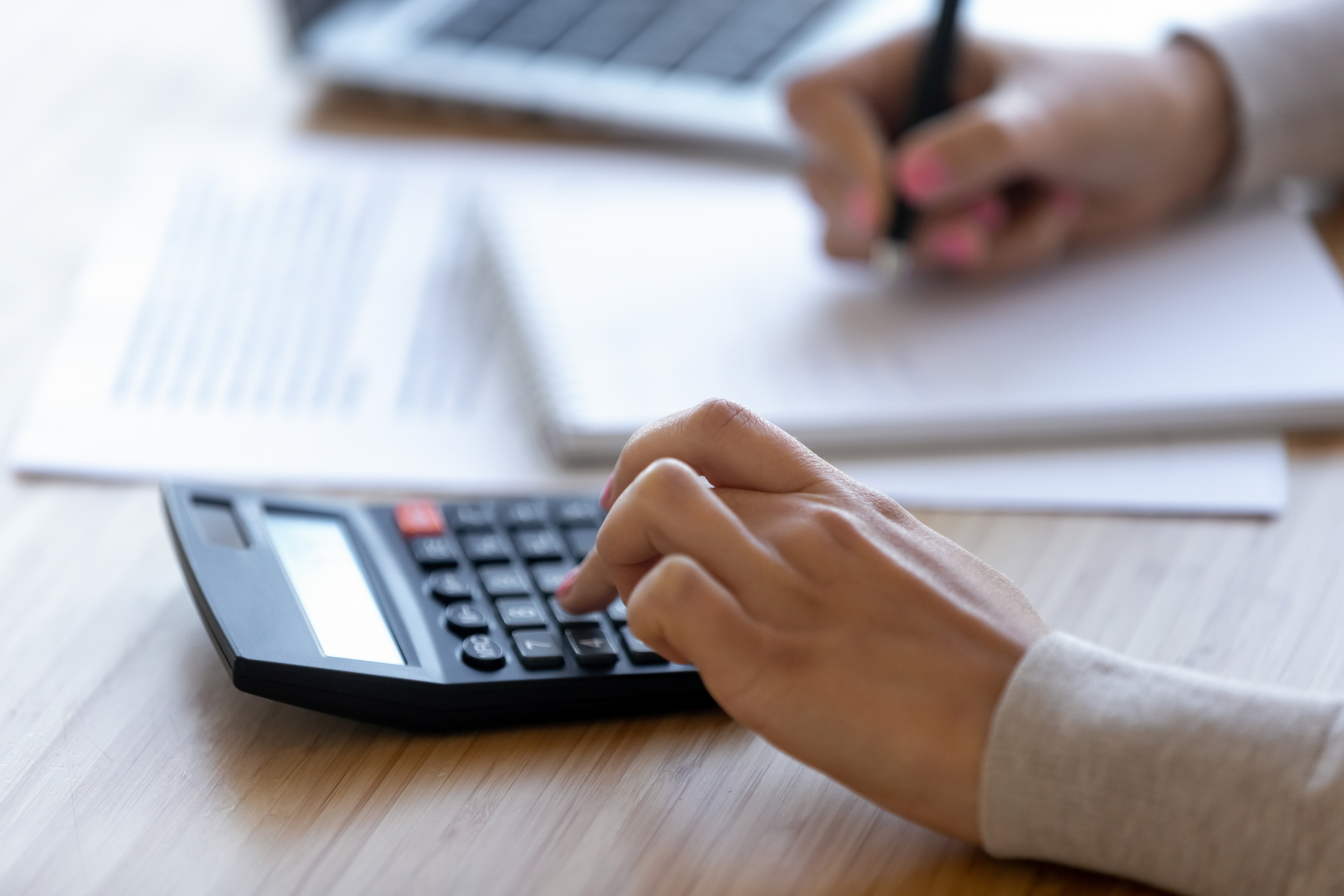 Female professional using calculator for business financial accounting, close up