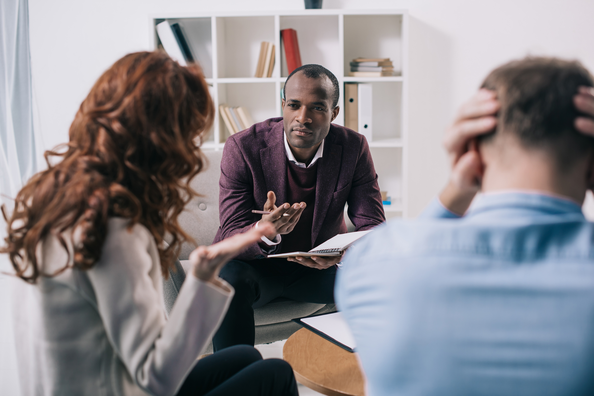 Frustrated divorcing couple and african american counselor in office