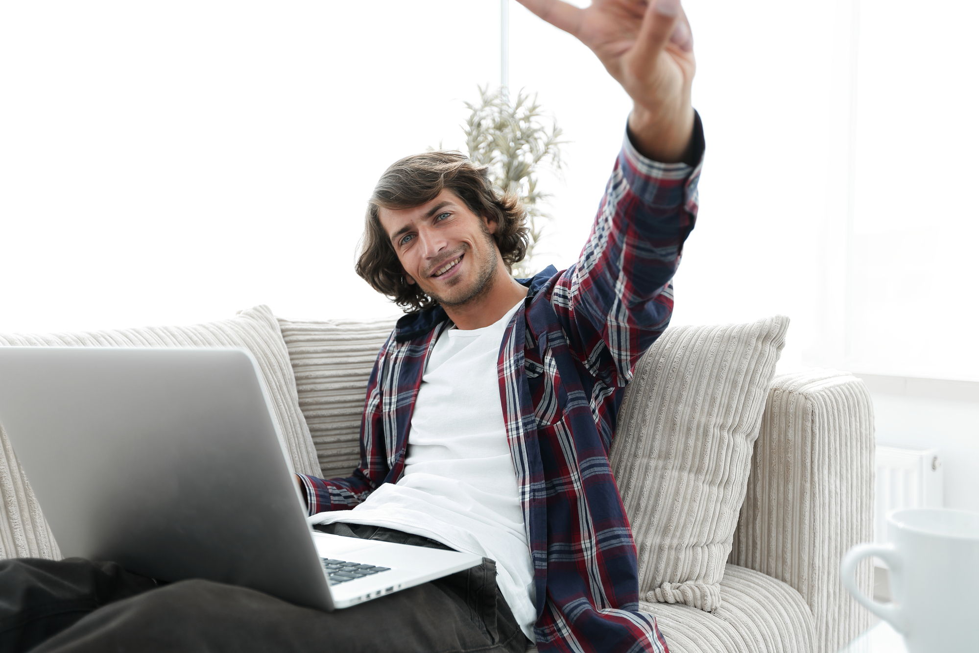 Happy guy with laptop sitting on sofa and showing his hand a winning gesture