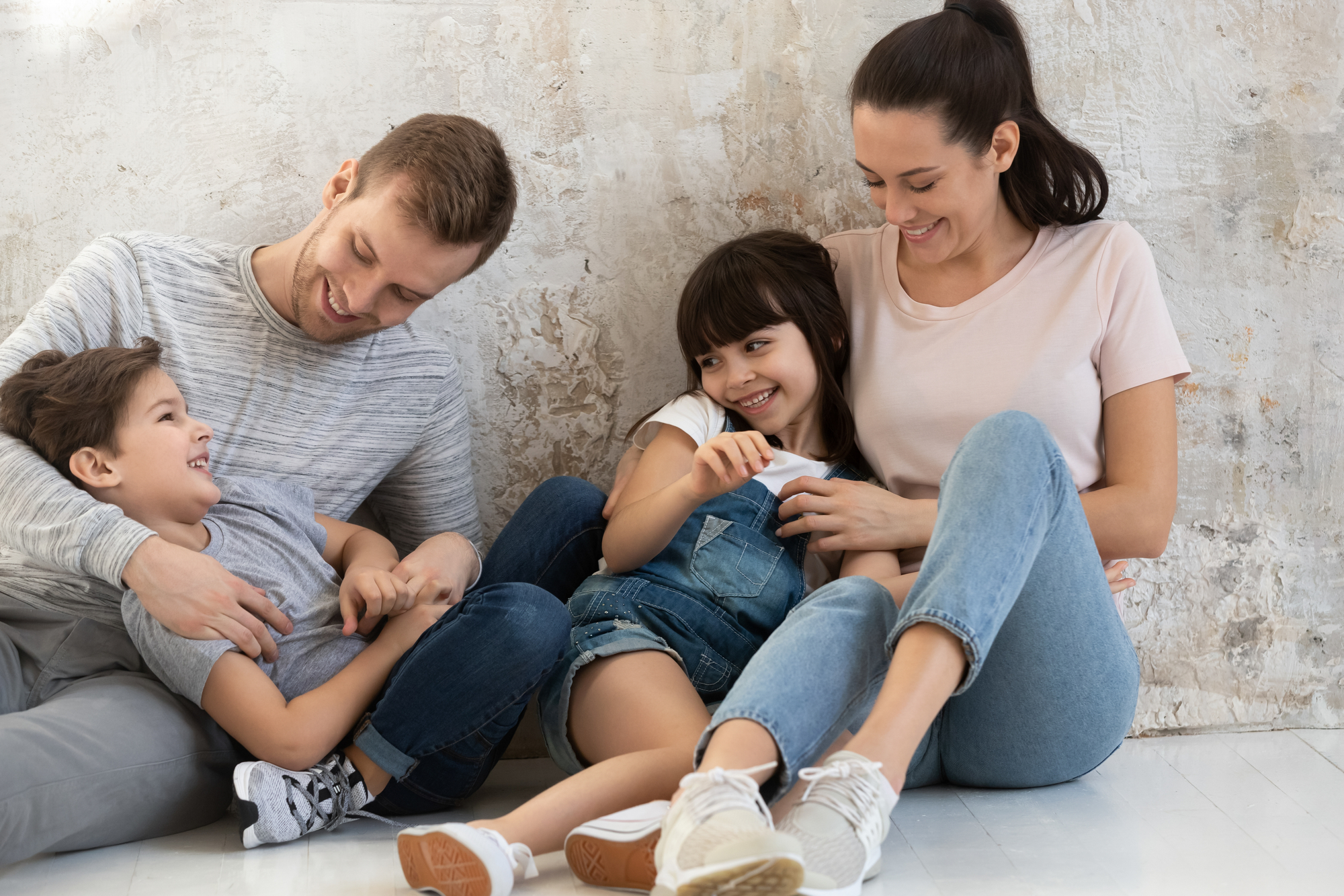 Happy parents and cute children playing tickling sit on floor