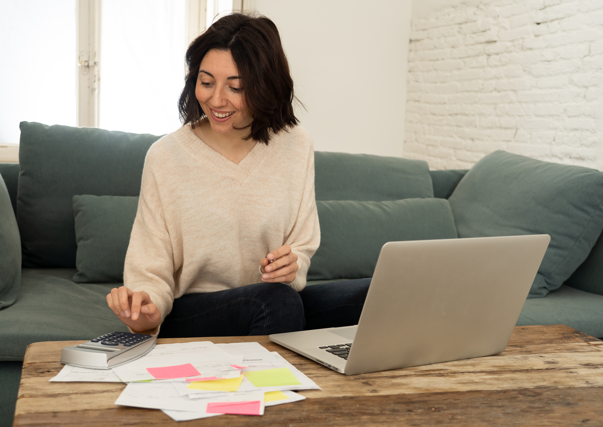 Happy young woman sitting on sofa surrounded by papers calculating expenses and paying bills