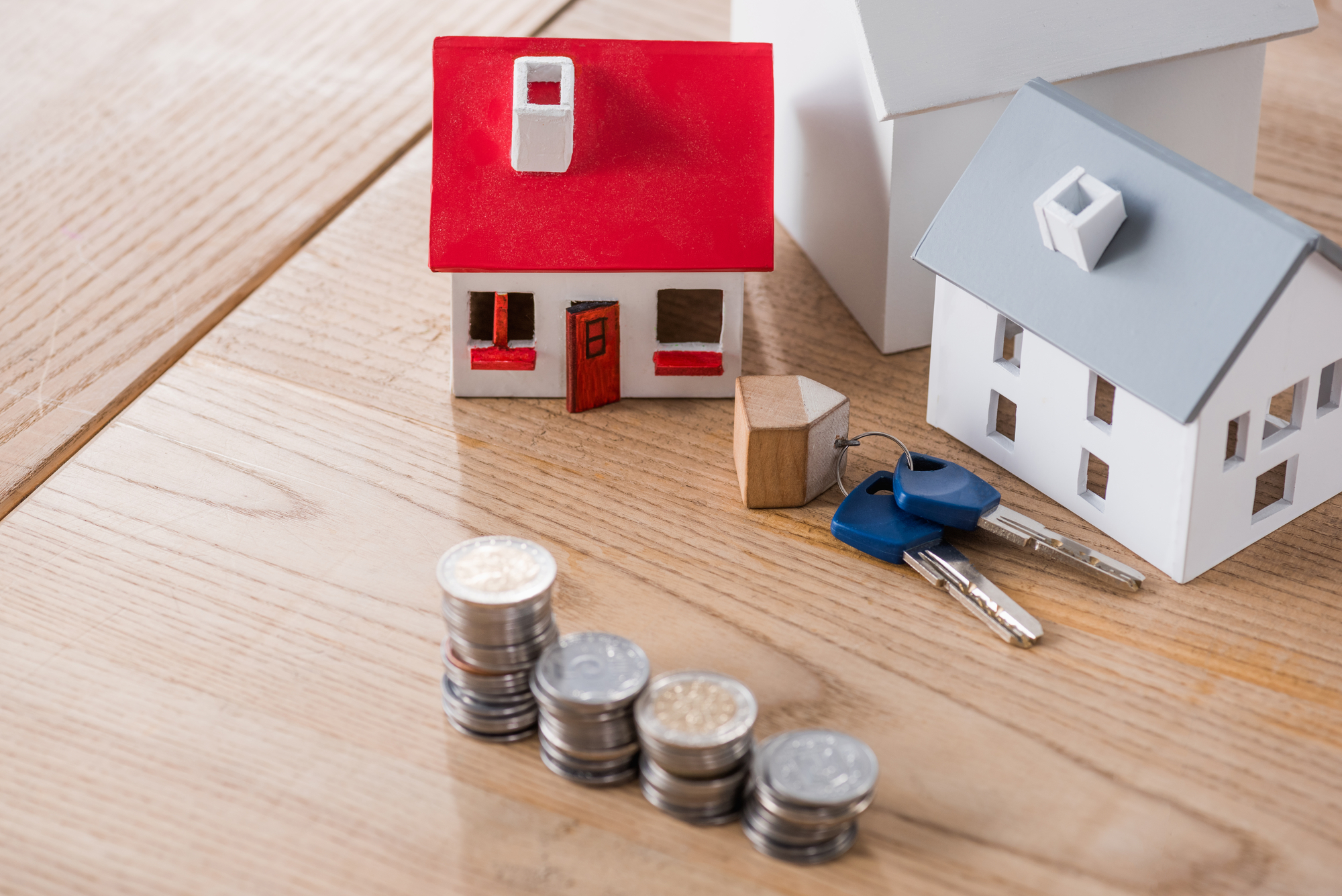 House models near keys and stacks of golden and silver coins on wooden table