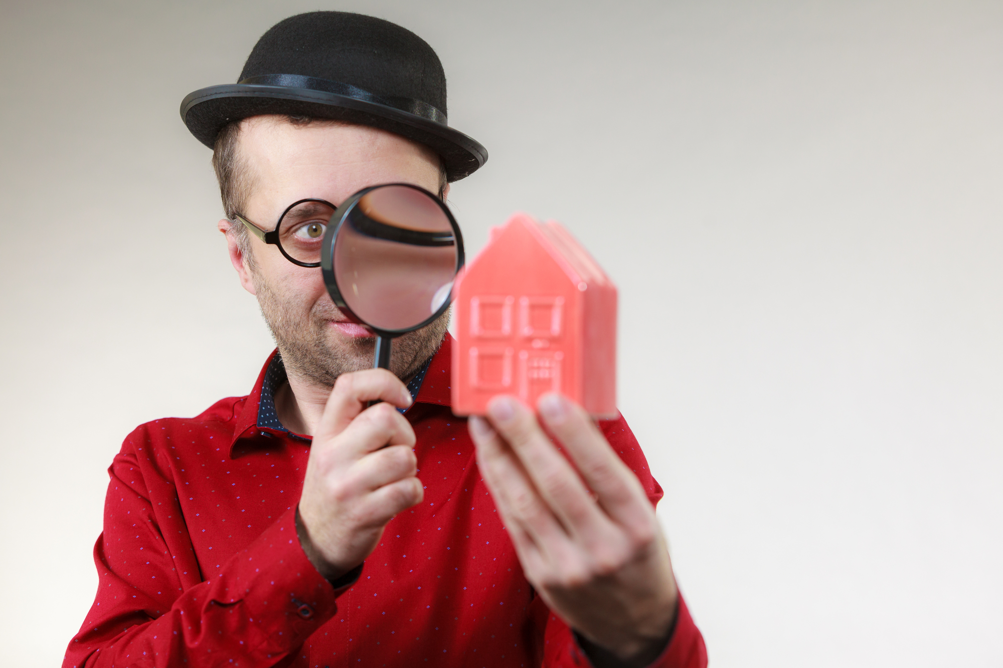 Man magnifying red house