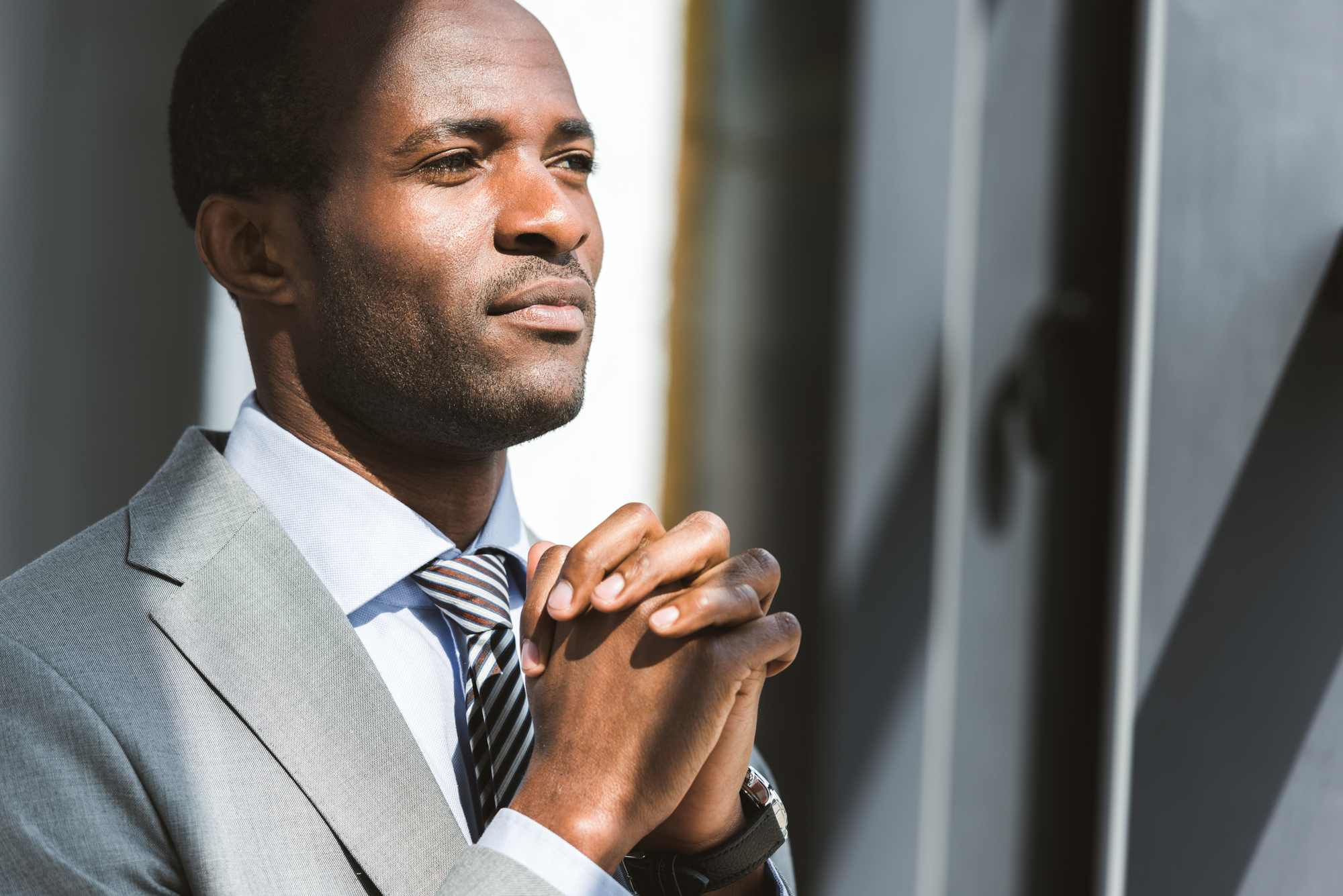 Portrait of handsome young african american businessman looking away