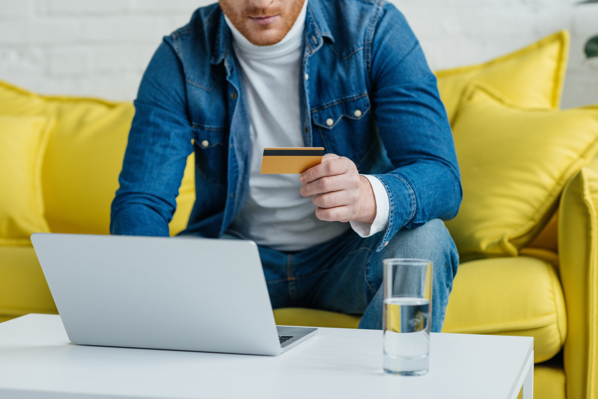 Young man holding credit card while using laptop